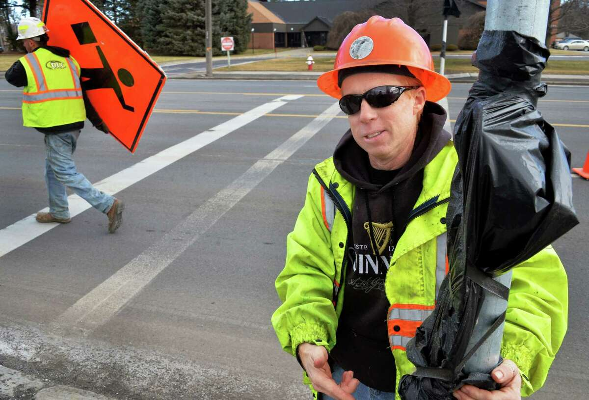 DOT engineer in charge Chris Roe, right, explains how the new pedestrian push buttons for traffic signals will work on Central Ave. near Reber St. Tuesday Feb. 2, 2016 in Colonie, NY. (John Carl D'Annibale / Times Union)