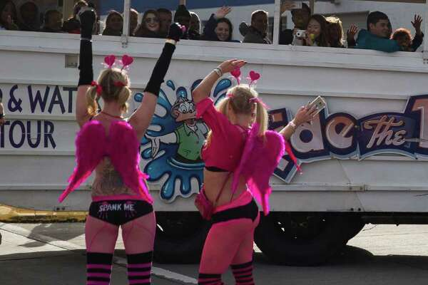 Two runners wave a t Ride the Ducks bus following Cupid's Undie Run at Lake Union Park in Seattle on Saturday. Feb. 20, 2016. The roughly mile-long run around Lake Union Park raises money for The Children's Tumor Foundation.