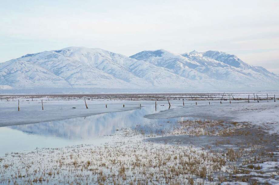 Snow covered mountains in the Wasatch range are reflected north of Ogden, Utah on Tuesday, Feb. 16, 2016. Photo: GRANT HINDSLEY, SEATTLEPI.COM / SEATTLEPI.COM
