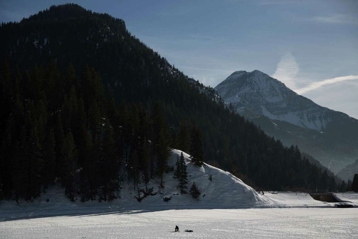 An ice fisherman drops his line in the shadow of Mt. Timpanogos in American Fork Canyon on Tibble Fork Reservoir in Utah, on Friday, Feb. 12, 2016.