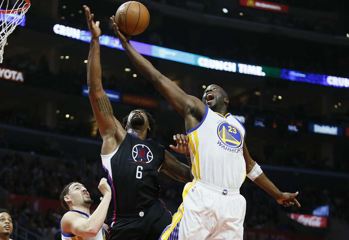 Warriors forward Draymond Green, right, reaches for a rebound over Clippers center DeAndre Jordan during the first half of Saturday's game in Los Angeles.