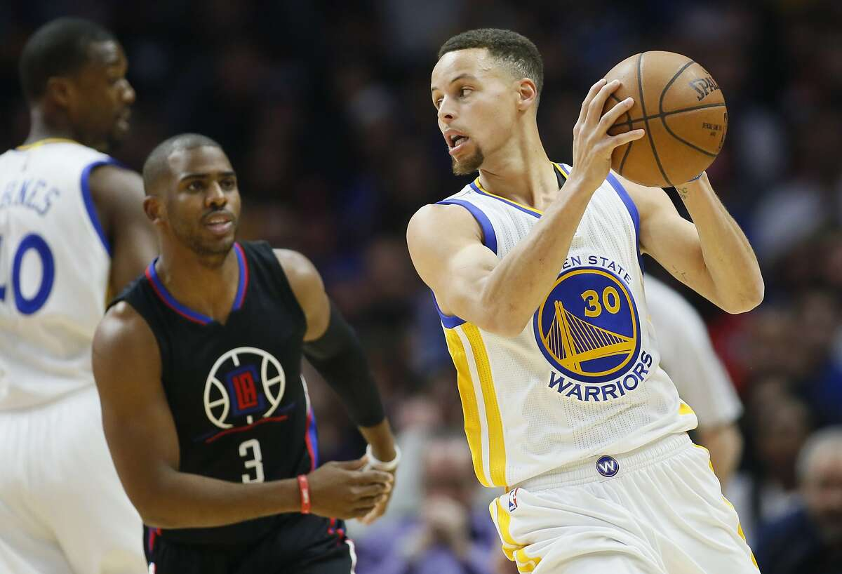 Golden State Warriors' Stephen Curry, right, controls the ball while Los Angeles Clippers' Chris Paul, left, defends during the first half of an NBA basketball game Saturday, Feb. 20, 2016, in Los Angeles. (AP Photo/Danny Moloshok)