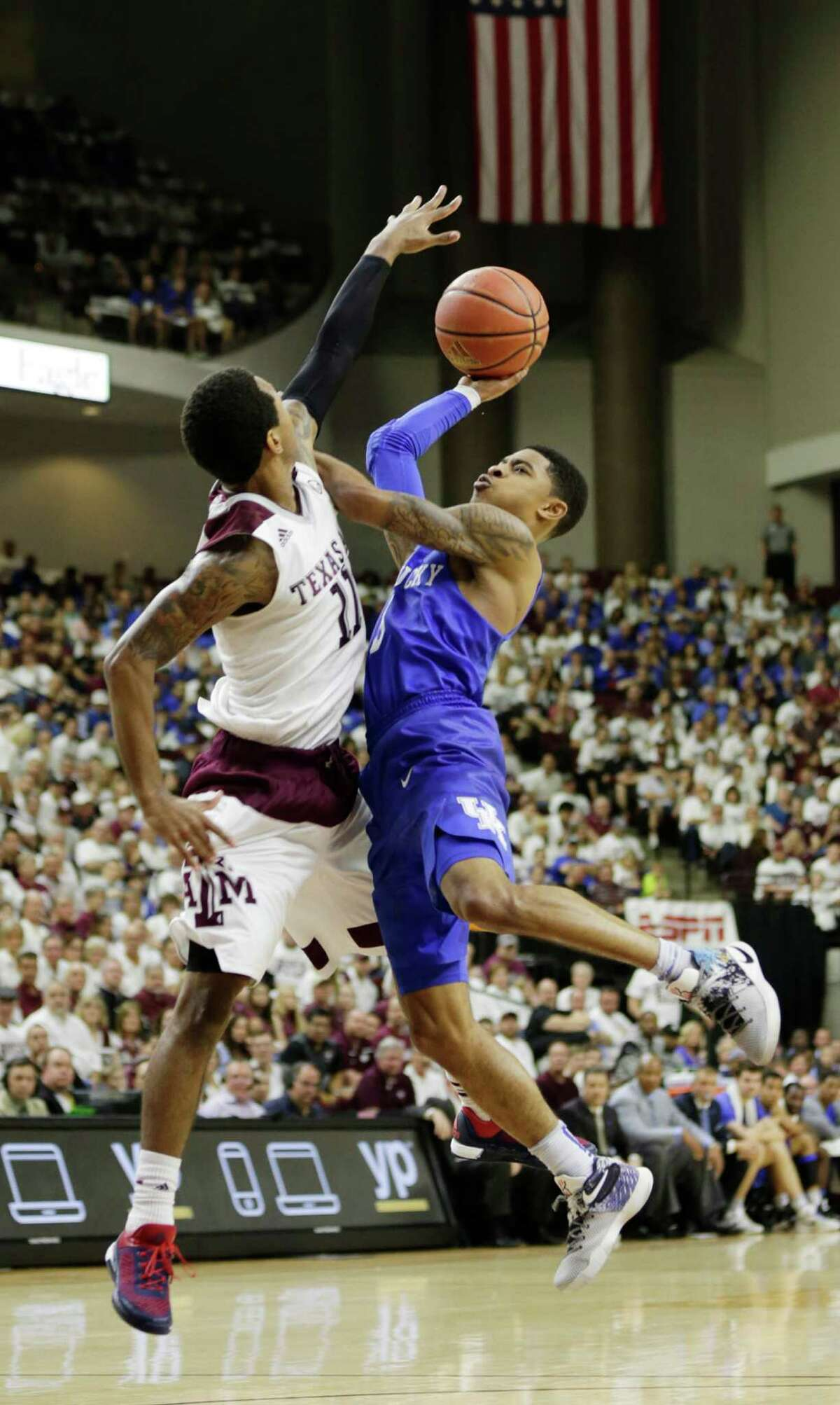 Texas A&M's Anthony Collins, left, fouls Kentucky's Tyler Ulis in the first half at Reed Arena in College Station, Texas, on Saturday, Feb. 20, 2016. The host Aggies won, 79-77, in overtime. (Pablo Alcala/Lexington Herald-Leader/TNS)
