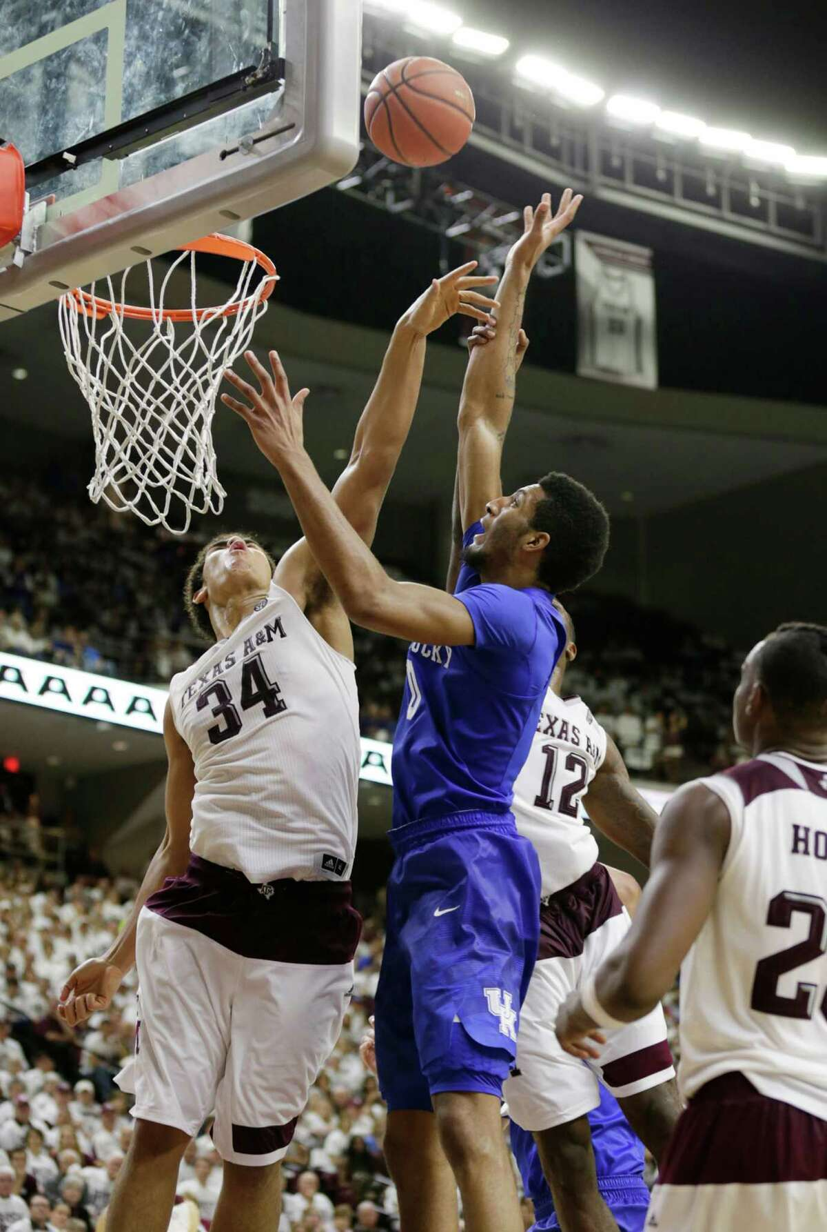 Texas A&M's Tyler Davis (34) bats a rebound away from Kentucky's Marcus Lee (00) in overtime at Reed Arena in College Station, Texas, on Saturday, Feb. 20, 2016. The host Aggies won, 79-77, in OT. (Pablo Alcala/Lexington Herald-Leader/TNS)