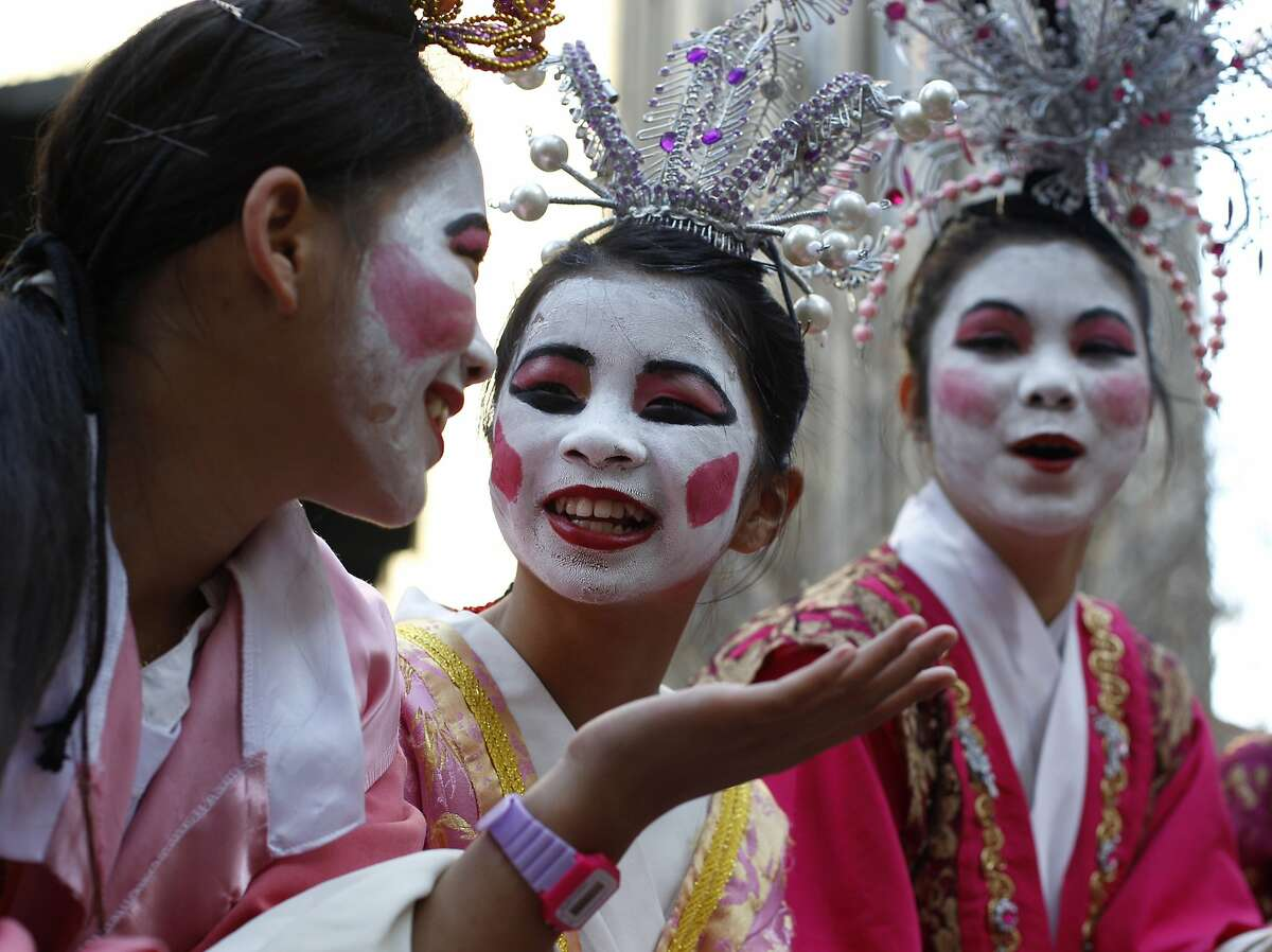 Students Tiffany Hui, left, Hailey Ng, and Hannah Yee from the West Portal Elementary School prepare for their performance at the annual Chinese New Year Parade in San Francisco, Calif., on Saturday Feb. 20, 2016