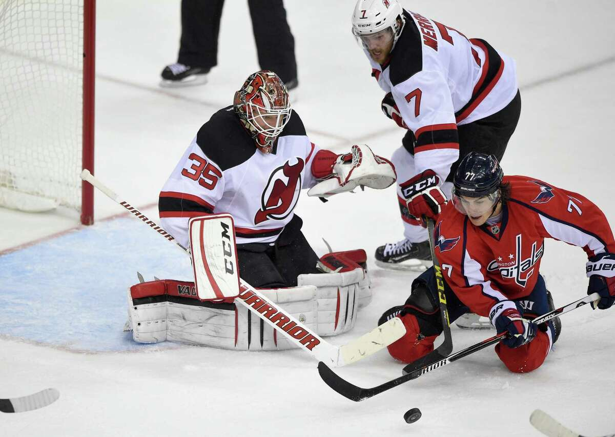 Washington Capitals right wing T.J. Oshie (77) battles for the puck against New Jersey Devils goalie Cory Schneider (35) and defenseman Jon Merrill (7) during the third period of an NHL hockey game, Saturday, Feb. 20, 2016, in Washington. The Capitals won 4-3. (AP Photo/Nick Wass) ORG XMIT: VZN131