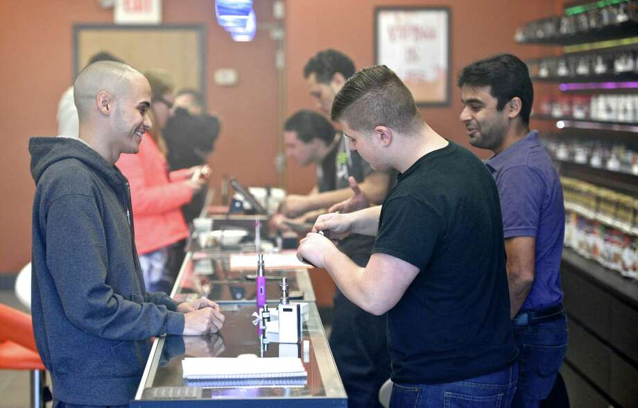 John Silva, of Danbury, left, samples vapor e-liquid flavors with the help of employee Michael Vallone at the Twilight Vapor shop on Hayestown Road in Danbury on Thursday. Photo: H John Voorhees III / Hearst Connecticut Media / The News-Times