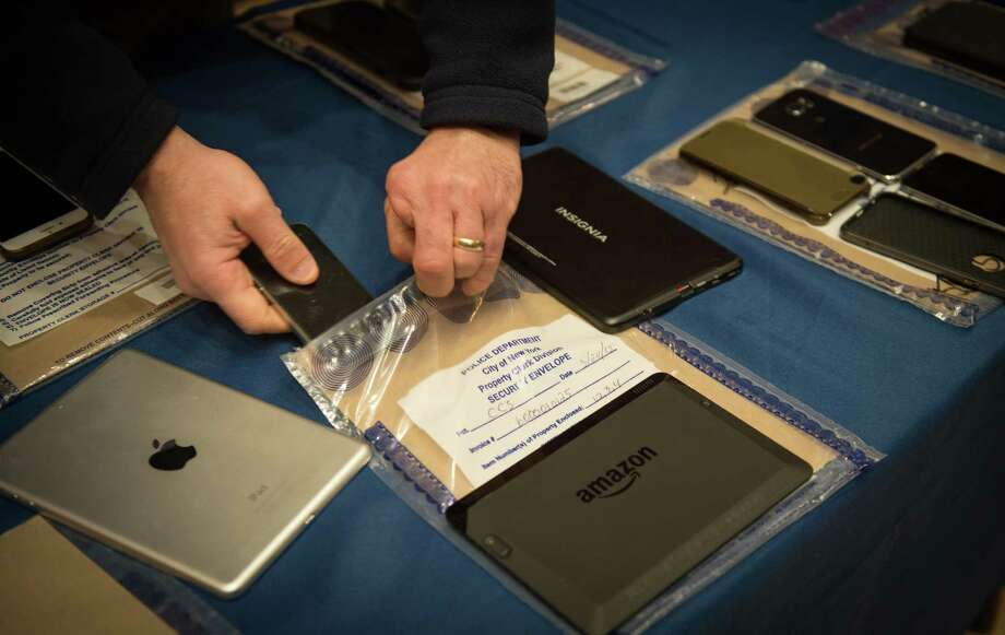 Encrypted smartphones held as evidence by the New York City Police Department are displayed at a news conference in New York, Feb. 18, 2016. Apple in the past has frequently helped the Justice Department unlock iPhones, but last fall, in connection with a routine drug case, it refused, foreshadowing a showdown with the Obama administration over the locked iPhone belonging to one of the San Bernardino shooting rampage suspects. (Bryan R. Smith/The New York Times) Photo: BRYAN R. SMITH, STR / New York Times / NYTNS