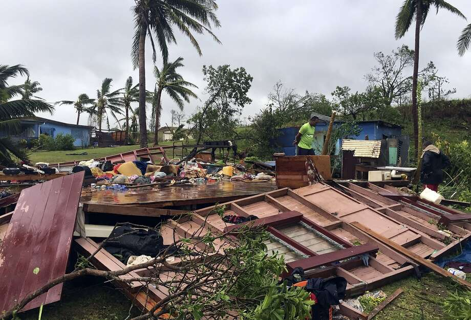 A family sifts through the remains of its home in Ba, Fiji, after it was struck by Cyclone Winston. Photo: Naziah Ali, AFP / Getty Images