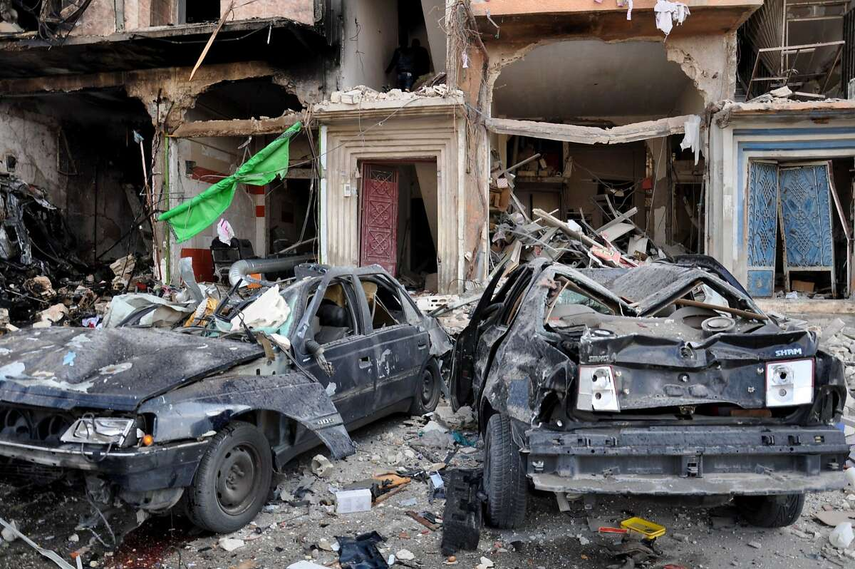 A picture taken on February 21, 2016 shows damaged cars at the site of a double car bomb attack in the Al-Zahraa neighborhood of the central Syrian city of Homs. Homs city is almost completely controlled by the Syrian government, and has regularly been targeted in bomb attacks. / AFP / STRINGERSTRINGER/AFP/Getty Images