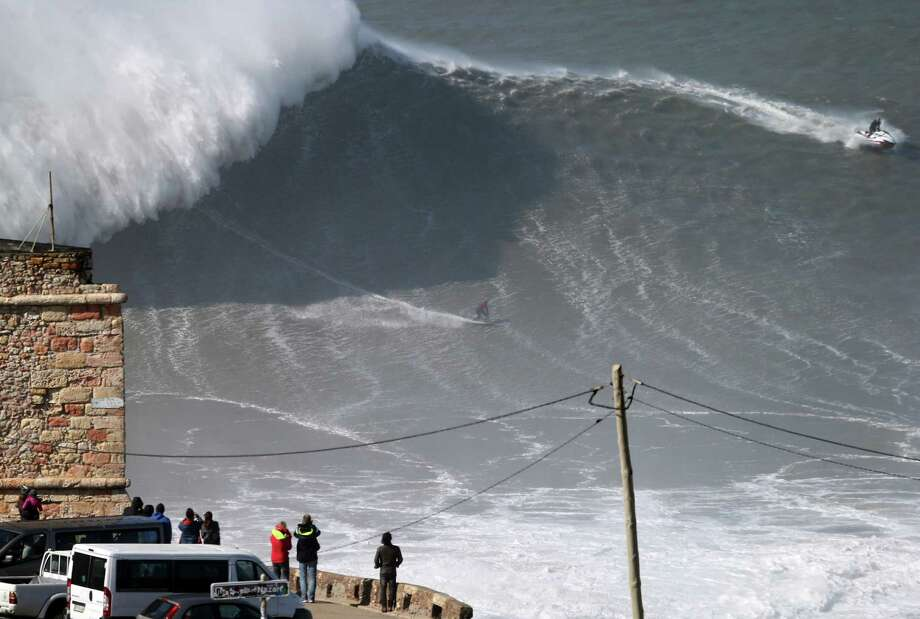 Nazare, Portugal, is a mecca for big-wave surfers. Here  Australian surfer Jarryd Foster tests his skill at the Praia do Norte, or North beach. Photo: Armando Franca, AP / AP