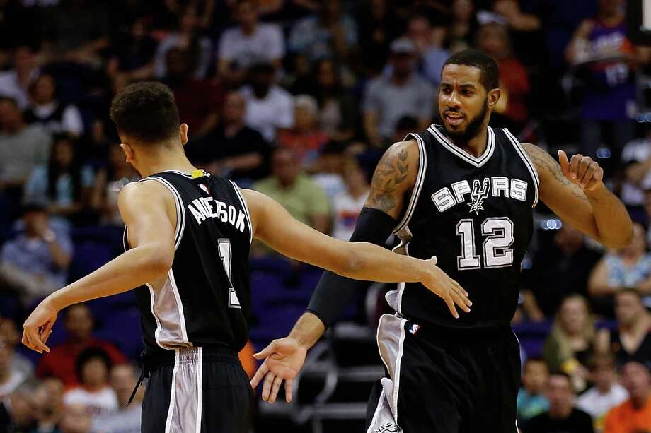 PHOENIX, AZ - FEBRUARY 21:  LaMarcus Aldridge #12 of the San Antonio Spurs high fives Kyle Anderson #1 after scoring against the Phoenix Suns during the first half of the NBA game at Talking Stick Resort Arena on February 21, 2016 in Phoenix, Arizona.  NOTE TO USER: User expressly acknowledges and agrees that, by downloading and or using this photograph, User is consenting to the terms and conditions of the Getty Images License Agreement. Photo: Christian Petersen, Getty Images / 2016 Getty Images