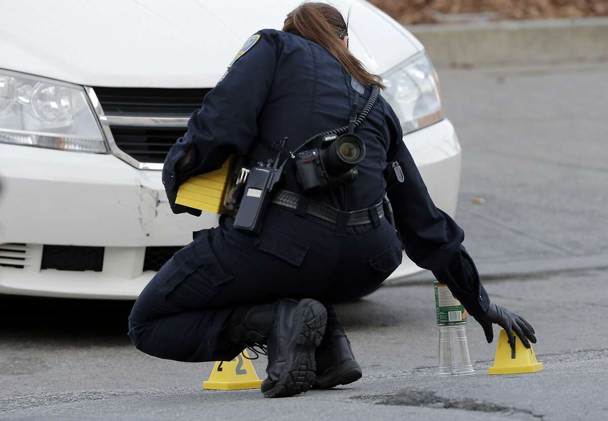 A San Francisco Police investigator places evidence markers on the street following a shooting on Fillmore Street in San Francisco, Calif., on Sunday, February 21, 2016, that left one person dead.