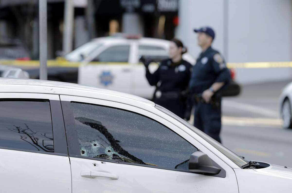 Bullet holes are visible in the passenger-side window of a car following a shooting on Fillmore Street in San Francisco, Calif., on Sunday, February 21, 2016, that left one person dead.