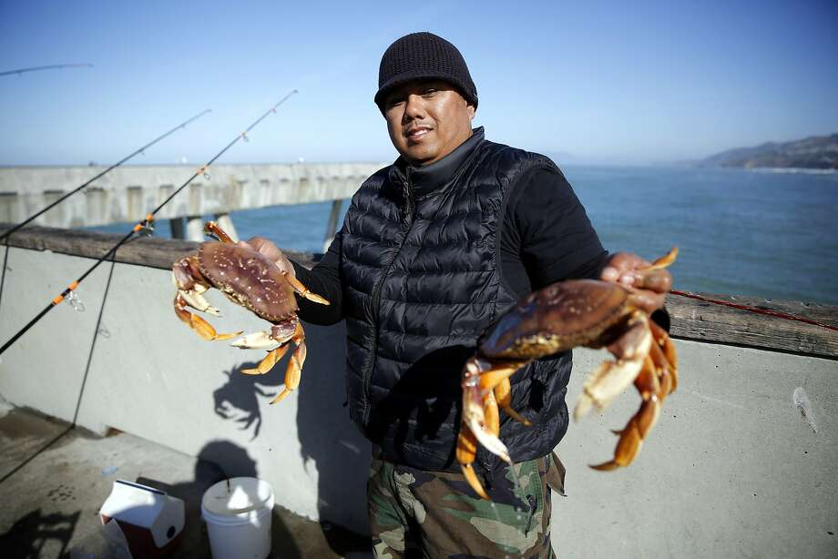 Jimmy Narag holds two of the crabs he caught off Pacifica Municipal Pier in Pacifica on Sunday, Feb. 21. Photo: Connor Radnovich, The Chronicle