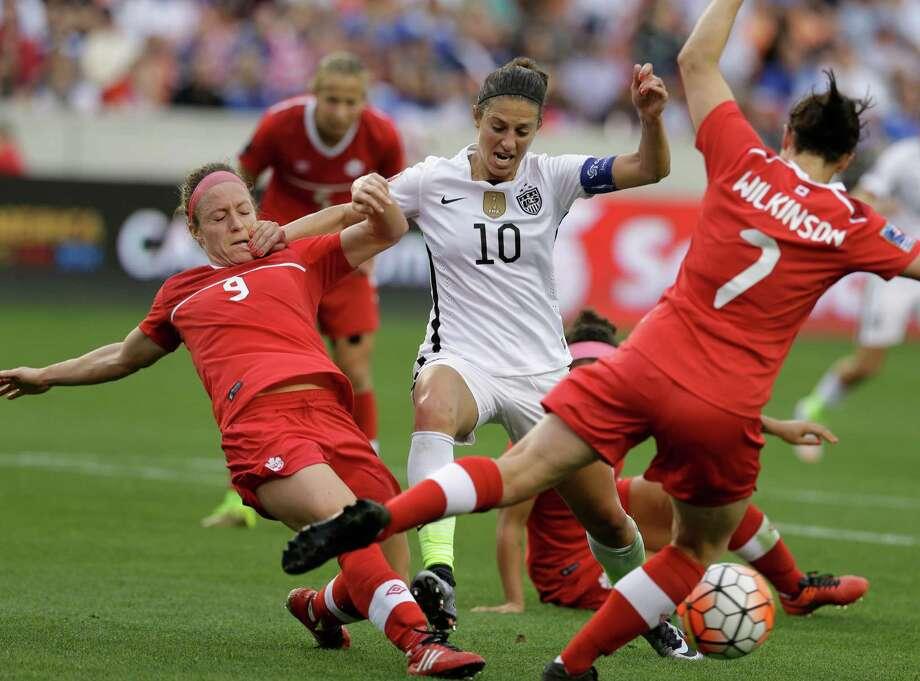 U.S. midfielder Carli Lloyd tries to negotiate in tight quarters against Canada's Josee Belanger, left, and Rhian Wilkinson. Photo: Melissa Phillip, Staff / © 2016 Houston Chronicle