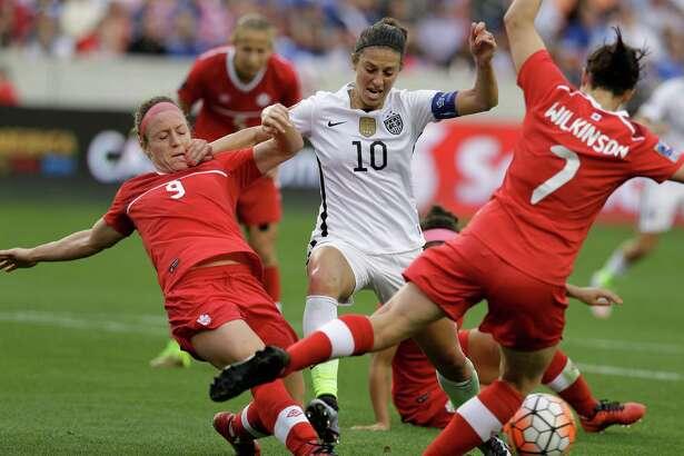 U.S. midfielder Carli Lloyd tries to negotiate in tight quarters against Canada's Josee Belanger, left, and Rhian Wilkinson.