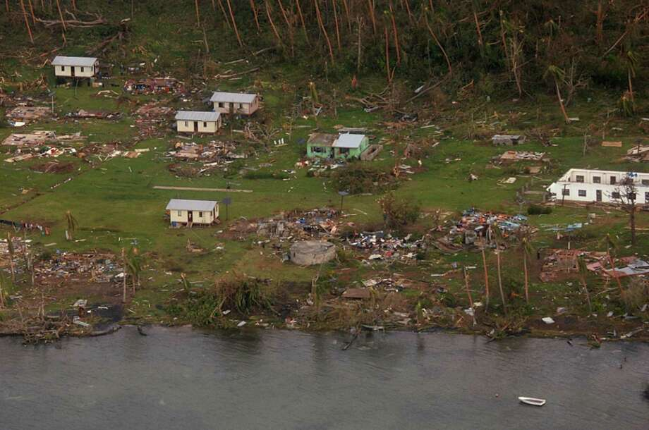 In this Sunday, Feb. 21, 2016 aerial photo supplied by the New Zealand Defense Force, debris is scattered around damaged buildings at Muamua on Vanua Blava Island in Fiji, after Cyclone Winston tore through the island nation. Fijians were finally able to venture outside Monday after authorities lifted a curfew but much of the country remained without electricity in the wake of a ferocious cyclone that left at least six people dead and destroyed hundreds of homes. (New Zealand Defense Force via AP) EDITORIAL USE ONLY Photo: Associated Press / New Zealand Defense Force