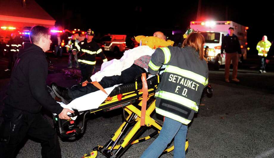 An unidentified survivor of a small plane crash is rushed to an ambulance In this Saturday, Feb. 20, 2016 after being rescued from Port Jefferson Harbor in Port Jefferson, N.Y.  The pilot and two other men aboard the plane were plucked from the frigid harbor after the plane crashed at about 11 p.m., officials said. A fourth unidentified passenger on board remained unaccounted for Sunday morning. (James Carbone, Newsday via AP) NYC LOCALS OUT; MANDATORY CREDIT ORG XMIT: NYANE101 Photo: James Carbone / Newsday