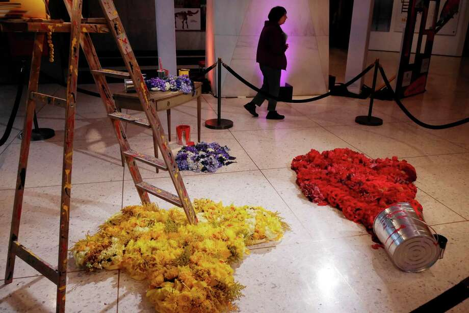 Visitors to the New York State Museum look over the floral display by David Michael Schmidt of Renaissance Florals Design at the New York in Bloom show on Sunday, Feb. 21, 2016, in Albany, N.Y.  The flowers were spread out to look like paint from paint cans.   (Paul Buckowski / Times Union) Photo: PAUL BUCKOWSKI / 10035510A