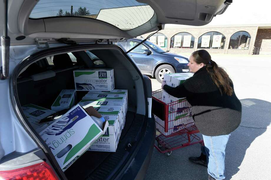 Michelle O'Leary loads up her car with bottled water for delivery to shut-ins and people who can't get the water themselves Friday Feb. 19, 2016, in Hoosick Falls, N.Y.     (Skip Dickstein/Times Union) Photo: SKIP DICKSTEIN / 10035468A