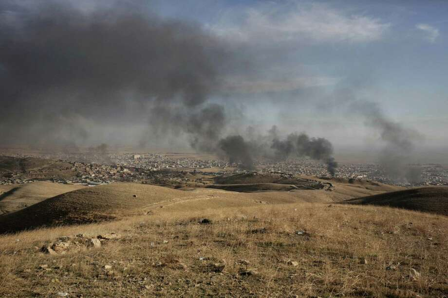 FILE -- In this  Nov. 12, 2015 file photo, smoke rises over Sinjar, northern Iraq from oil fires set by Islamic State militants as Kurdish Iraqi fighters, backed by U.S.-led airstrikes, launch a major assault. Plunging oil prices have pitched Iraq into a severe financial crisis as it struggles to combat the Islamic State group, play host to millions of refugees and rebuild cities and towns ravaged by war. Many of the Kurdish fighters known as the peshmerga -- longtime U.S. allies who have been among the most effective forces battling the IS group -- are not being paid, an Iraqi official said. (AP Photo/Bram Janssen, File) Photo: Bram Janssen, STF / Associated Press / AP
