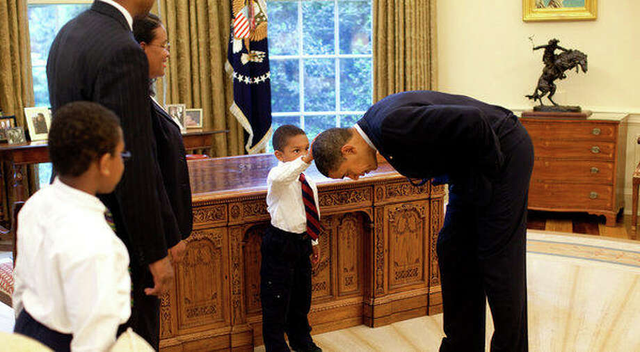 President Barack Obama bends over so the son of a White House staff member can pat his head during a family visit to the Oval Office May 8, 2009. The youngster wanted to see if the President's haircut felt like his own. Photo: Pete Souza, The White House
