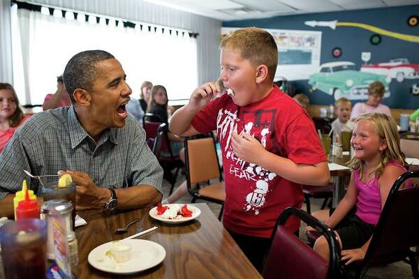 President Barack Obama shares his strawberry pie with a boy during a lunch stop at Kozy Corners restaurant in Oak Harbor, Ohio, July 5, 2012.