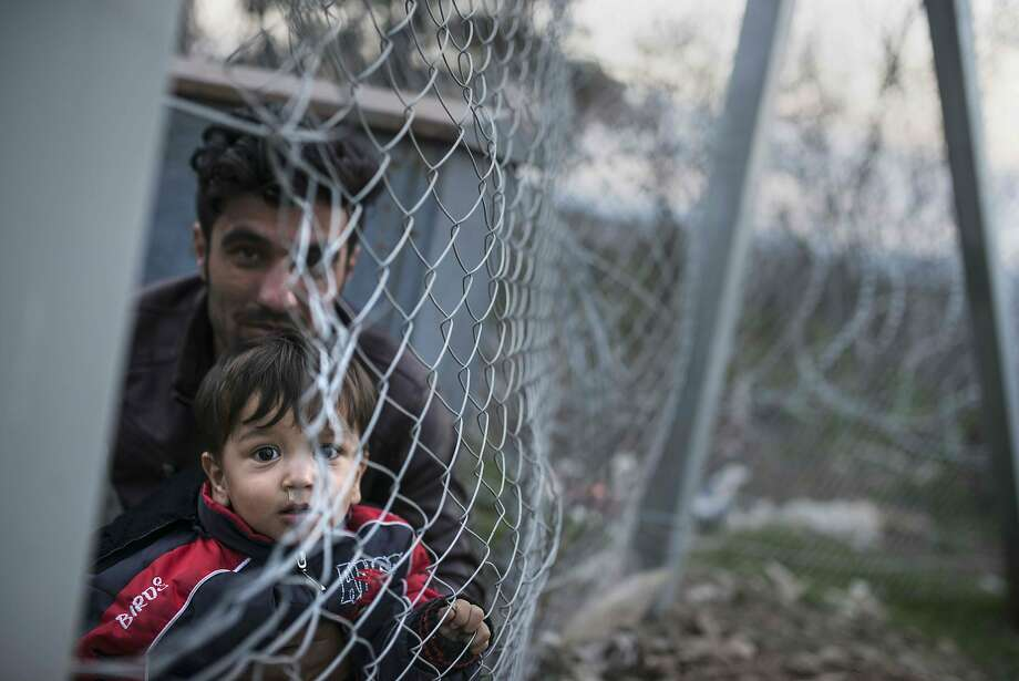 A man holds a boy at the Greek border fence near Gevgelija, Macedonia, where Afghans were being barred from crossing. Photo: Robert Atanasovski, AFP / Getty Images