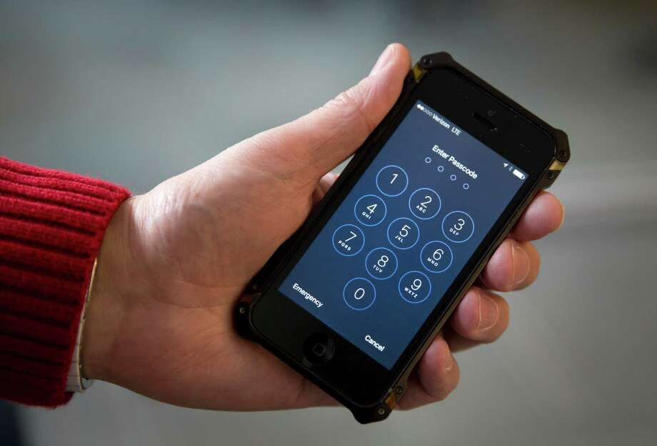 An iPhone is seen in Washington, Wednesday, Feb. 17, 2016. A U.S. magistrate judge has ordered Apple to help the FBI break into a work-issued iPhone used by one of the two gunmen in the mass shooting in San Bernardino, California, a significant legal victory for the Justice Department in an ongoing policy battle between digital privacy and national security. Apple CEO Tim Cook immediately objected, setting the stage for a high-stakes legal fight between Silicon Valley and the federal government. (AP Photo/Carolyn Kaster) Photo: Carolyn Kaster / Associated Press / AP
