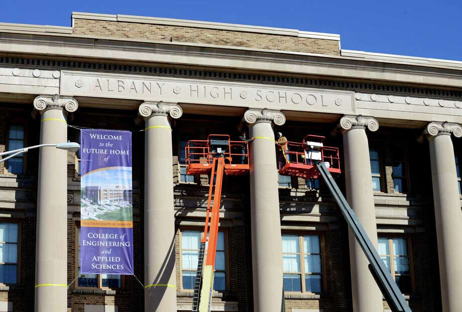 University at Albany workers erect new signs on the former Albany High School building at the UAlbany downtown campus on Monday, Feb. 22, 2016, on Western Avenue in Albany, N.Y. The University at Albany plans to turn the former high school into an engineering school. It will be modernized and renovated into a teaching and research facility. UAlbany is seeking $20 million in capital funding for the initial stages of renovation, according to a press release from the university. (Will Waldron/Times Union) Photo: Will Waldron