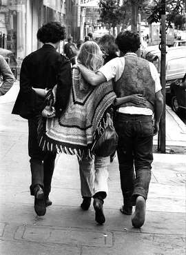 """An embracing threesome walks down Haight - a unique sight since the violence in  Haight [in 1967].'"