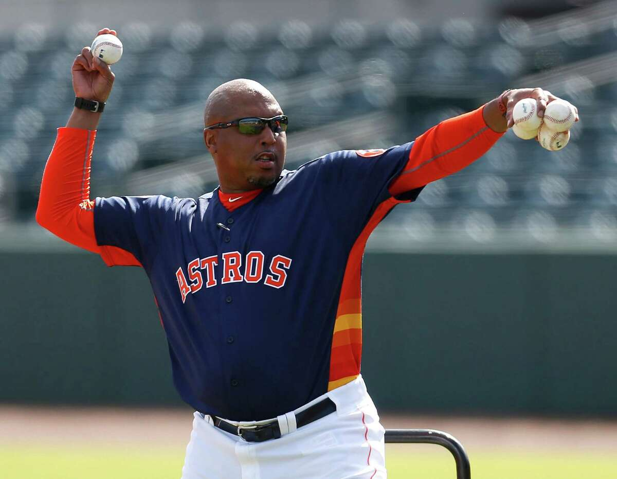 Houston Astros assistant hitting coach Alonzo Powell pitches during batting practice for position players on the main field during spring training in Kissimmee, Florida, Monday, Feb. 22, 2016.