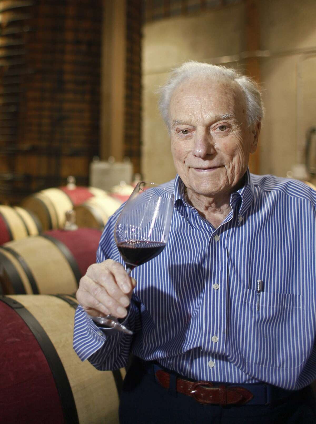 In this Nov. 4, 2009 file photo, Peter Mondavi holds a glass of Cabernet Sauvignon inside the original Redwood Cellar at the Charles Krug Winery in St. Helena, Calif.