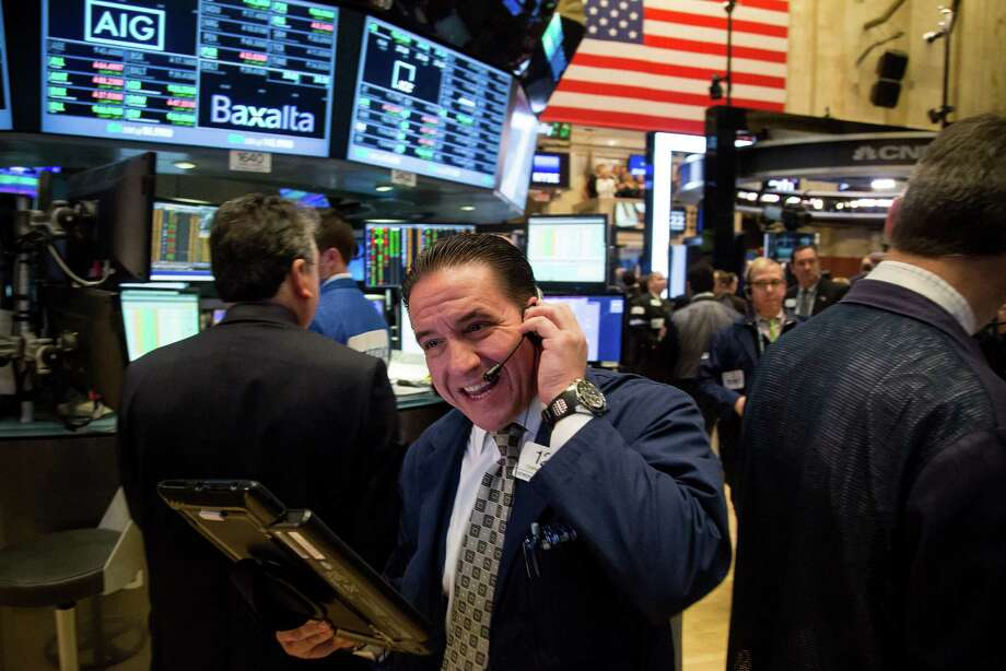 Traders enjoy a positive workday Monday on the floor of the New York Stock Exchange. Stocks across the globe rallied, and all three major U.S. stock indices inched upward. Photo: Michael Nagle / Bloomberg / Bloomberg