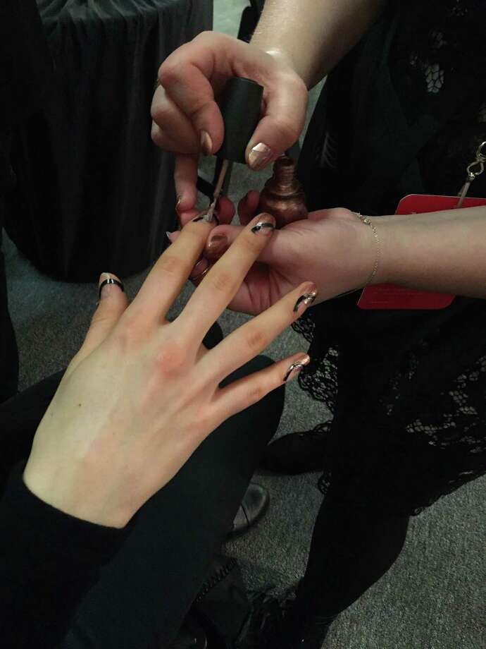 A nail technician creates a negative space manicure with French manicure strips and China Glaze nail polish backstage at the Alice + Olivia fashion presentation Feb. 16. Photo: Sara Bauknecht /TNS / Pittsburgh Post-Gazette