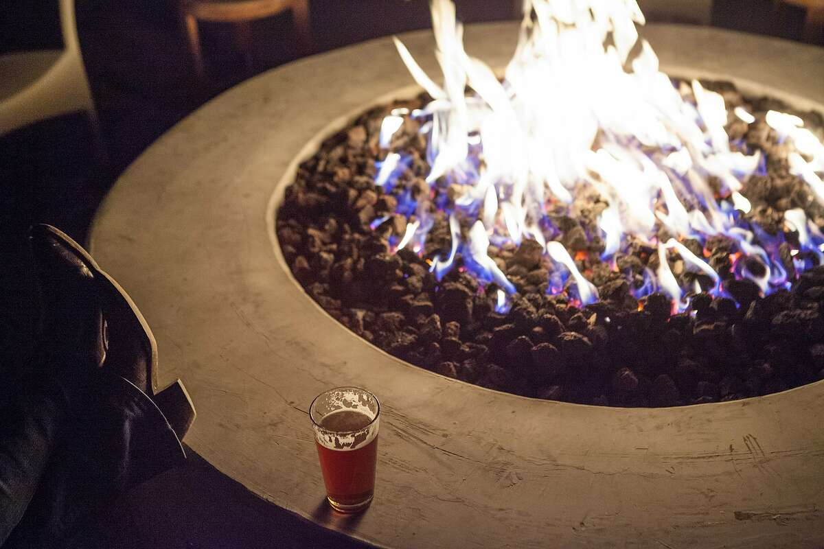 Staying warm with a pint of beer sitting at the fire-pit at Sam's Social located at Indian Springs Resort in Calistoga.