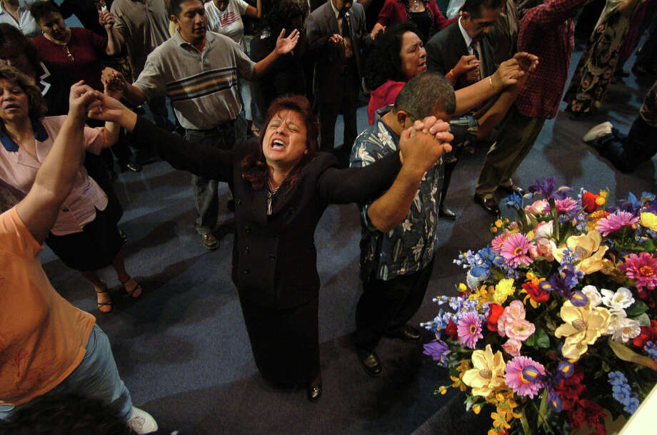 Believers join hands in prayer during a Sunday service at The Miracle Center Church in this file photo from 2005. The church on the South Side was founded in 1980 by Pastor Ruben Medel. Photo: BILLY CALZADA /SAN ANTONIO EXPRESS-NEWS / SAN ANTONIO EXPRESS-NEWS