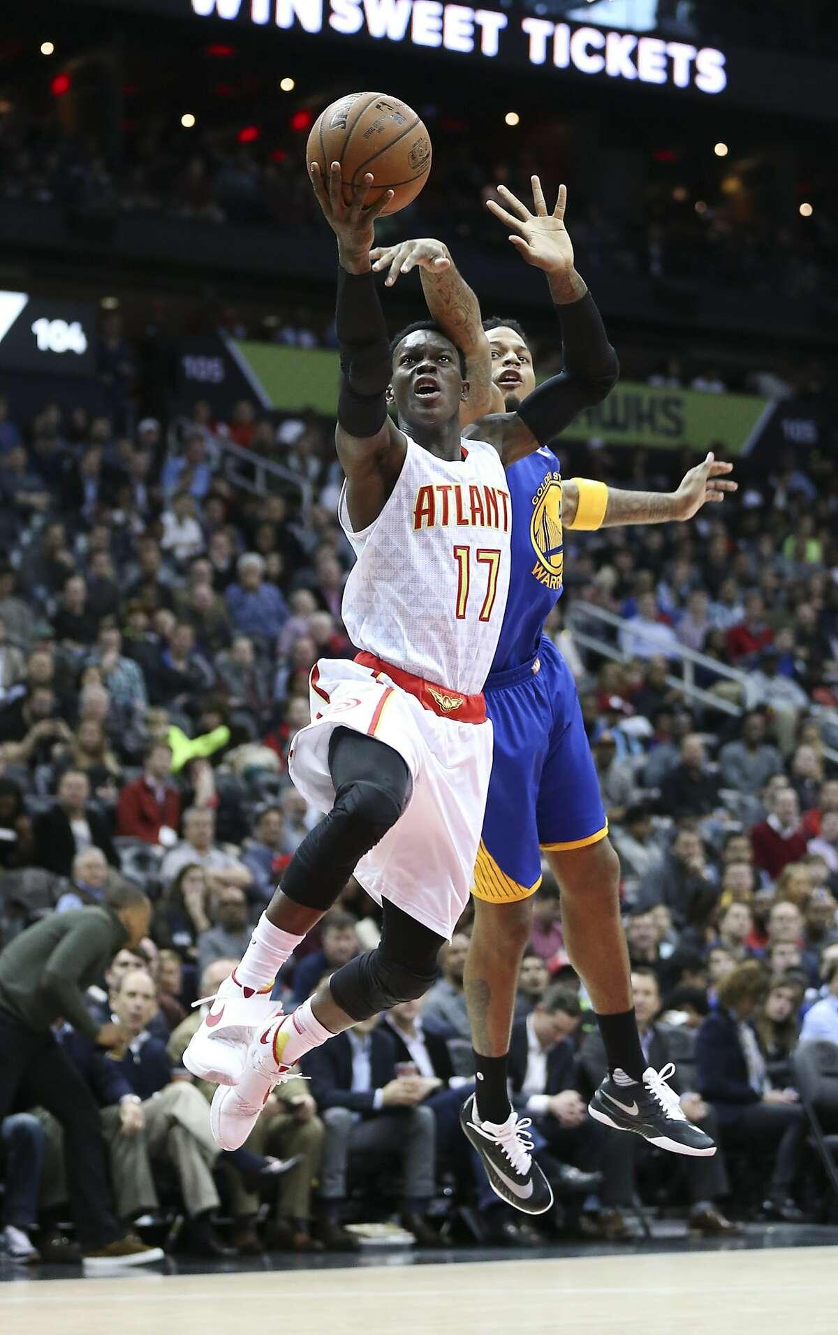 Atlanta Hawks guard Dennis Schroder (17) shoots as Golden State Warriors forward Brandon Rush (4) defends in the first half of an NBA basketball game Monday, Feb. 22, 2016, in Atlanta.