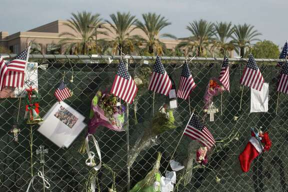 Memorial items hang from a fence around the Inland Regional Center, the site in San Bernardino, Calif., where two attackers killed 14 people. Apple has been ordered to bypass its iOS9's security to get data from one of the attacker's phones.