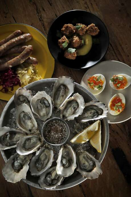 Happy hour offerings at Bar Agricole in S.F. Shown here: Hammersley oysters with mignonette (left), pork sausages with sauerkraut and mustart; soft-boiled egg with creme fraiche and salmon roe; and pig's head fritters with pickled chiles, Photo: Carlos Avila Gonzalez, The Chronicle