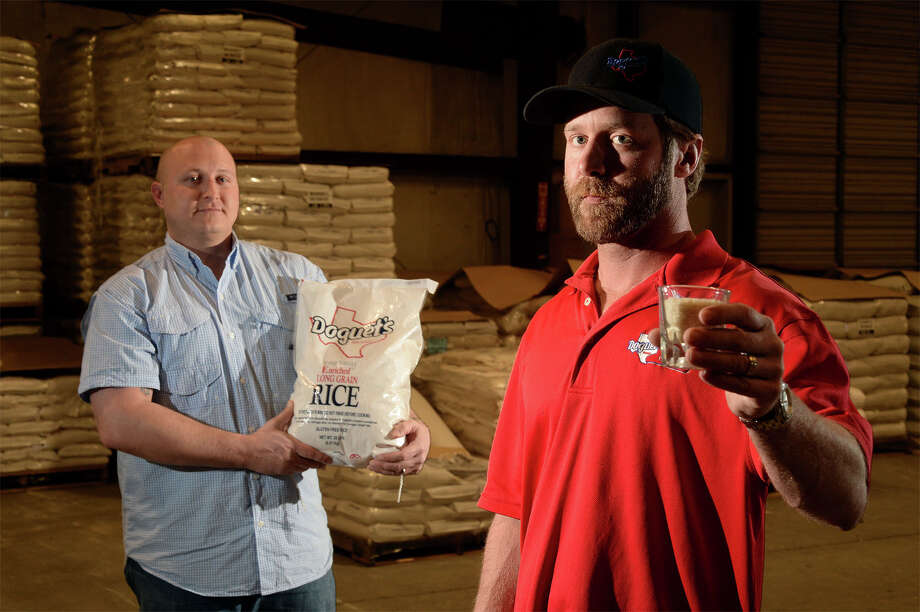 Doguet Rice is making a move to enter the spirits industry with a rice based vodka that is expected to hit the market in late 2016. From left, Darby Doguet holds a bag of Doguet rice and Greg Devillier holds a shot glass filled with rice at Doguet's in Beaumont on Friday.  