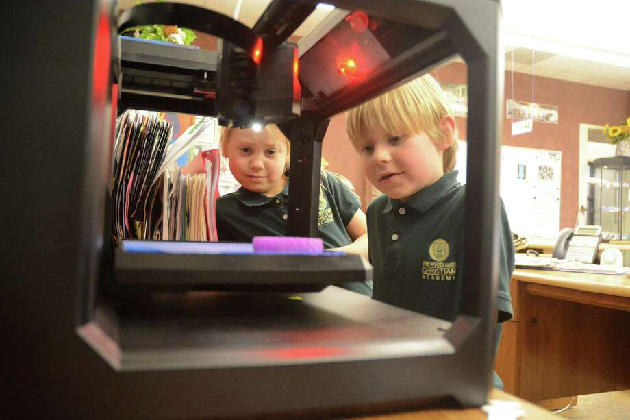 First graders Avery Rook and Banner Carlson watch a 3D printer produce an art project at The Woodlands Christian Academy. Photo: David Hopper, For The Chronicle / freelance