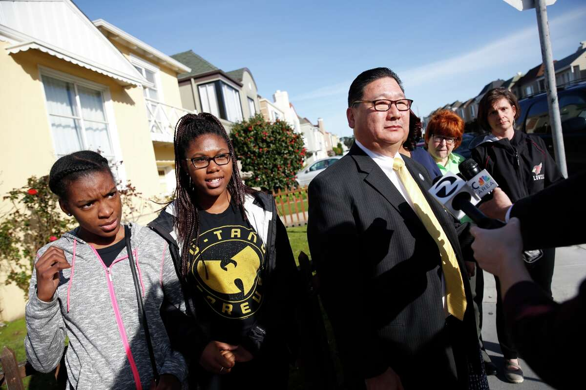 Lowell High School students Cierra Dunn (left), junior, 16, and Cyy'na Davis (second from left), sophomore, 15, link arms as they stand next to Lowell High School principal Andrew Ishibashi (third from left) as he makes a statement to the media while assistant principals Holly Giles (partially seen third from right), Dacotah Swett (second from right), and Margaret Peterson (right) stand alongside on Eucalyptus Drive on Tuesday, February 23, 2016 in San Francisco.