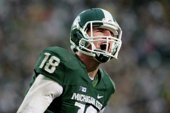 In this Nov. 2, 2013, file photo,  Michigan State quarterback Connor Cook yells in celebration after scoring a touchdown against Michigan during an NCAA college football game, in East Lansing, Mich. Cook finished the 2013 season strong, throwing for 304 yards and three touchdowns against Ohio State in the Big Ten championship game and for a career-high 332 yards and two TDs against Stanford while being named Offensive MVP of the Rose Bowl. (AP Photo/Al Goldis)
