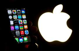 (FILES) This file photo taken on January 30, 2015 shows an illustration of an iPhone held up in front of the Apple Inc. logo. Apple said February 22, 2016 it would accept having a panel of experts consider access to encrypted devices if US authorities drop efforts to force it to help break into the iPhone of a California attacker. / AFP / PHILIPPE HUGUENPHILIPPE HUGUEN/AFP/Getty Images