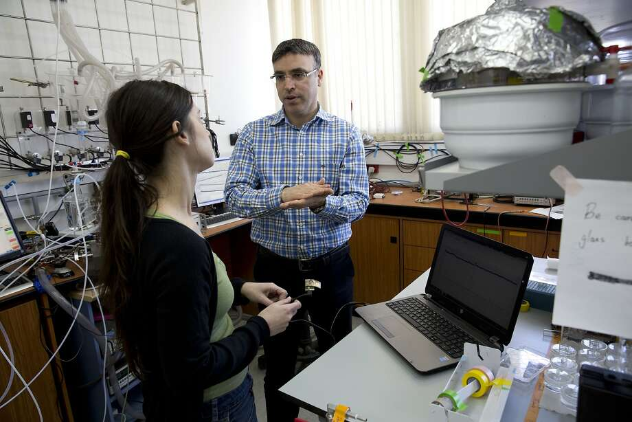 Professor Hossam Haick  talks to a researcher in his lab  in Haifa. Photo: Dusan Vranic, Associated Press
