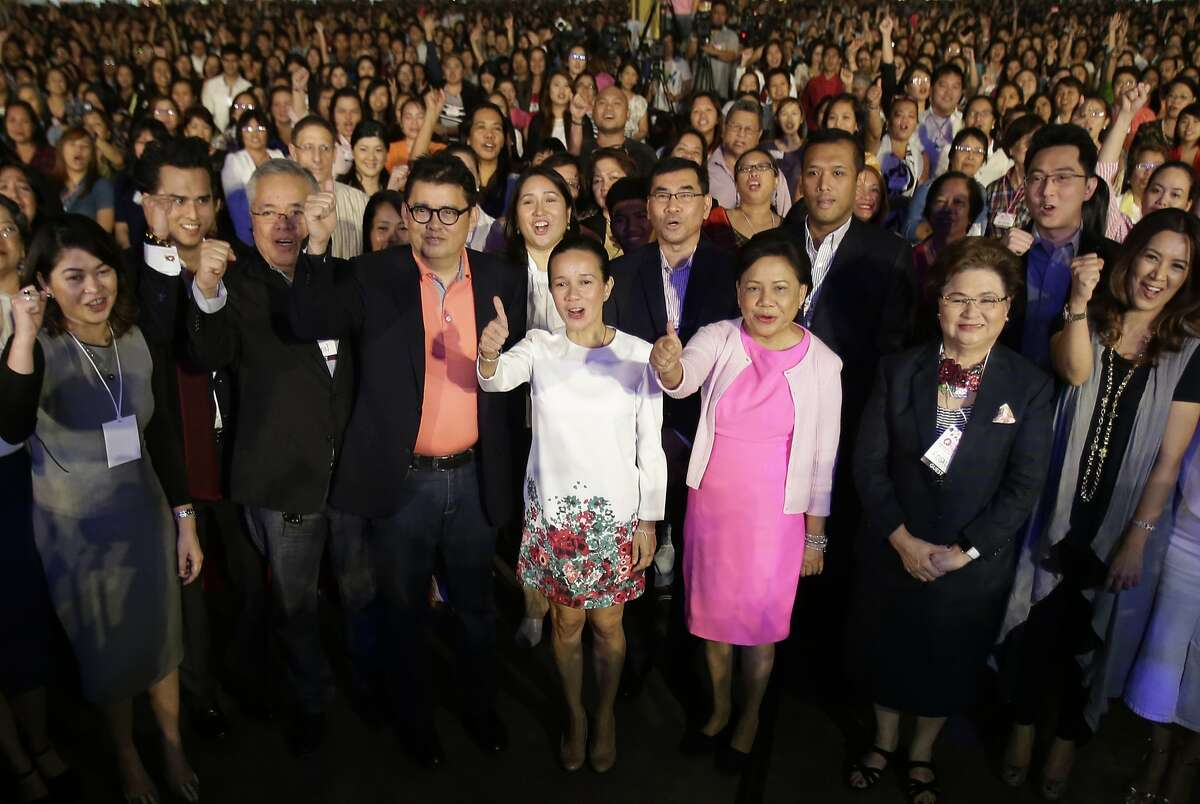 FILE - In this Feb. 18, 2016 file photo, Sen. Grace Poe, center, a presidential hopeful, poses beside Sen. Cynthia Villar, third right, entrepreneurs and students during an Entrepreneurship Summit in suburban Pasay, south of Manila, Philippines. Poe, 47, has seen her popularity soar since she first ran for office three years ago. She is the adopted daughter of one of the country's most famous movie couples. Her late father mostly played roles as a defender of the downtrodden in a country still plagued by widespread poverty and corruption. But the Commission on Elections ruled in December that Poe was not a natural-born Filipino as required by the Constitution because she was abandoned as a baby by her unknown parents at a Roman Catholic church.