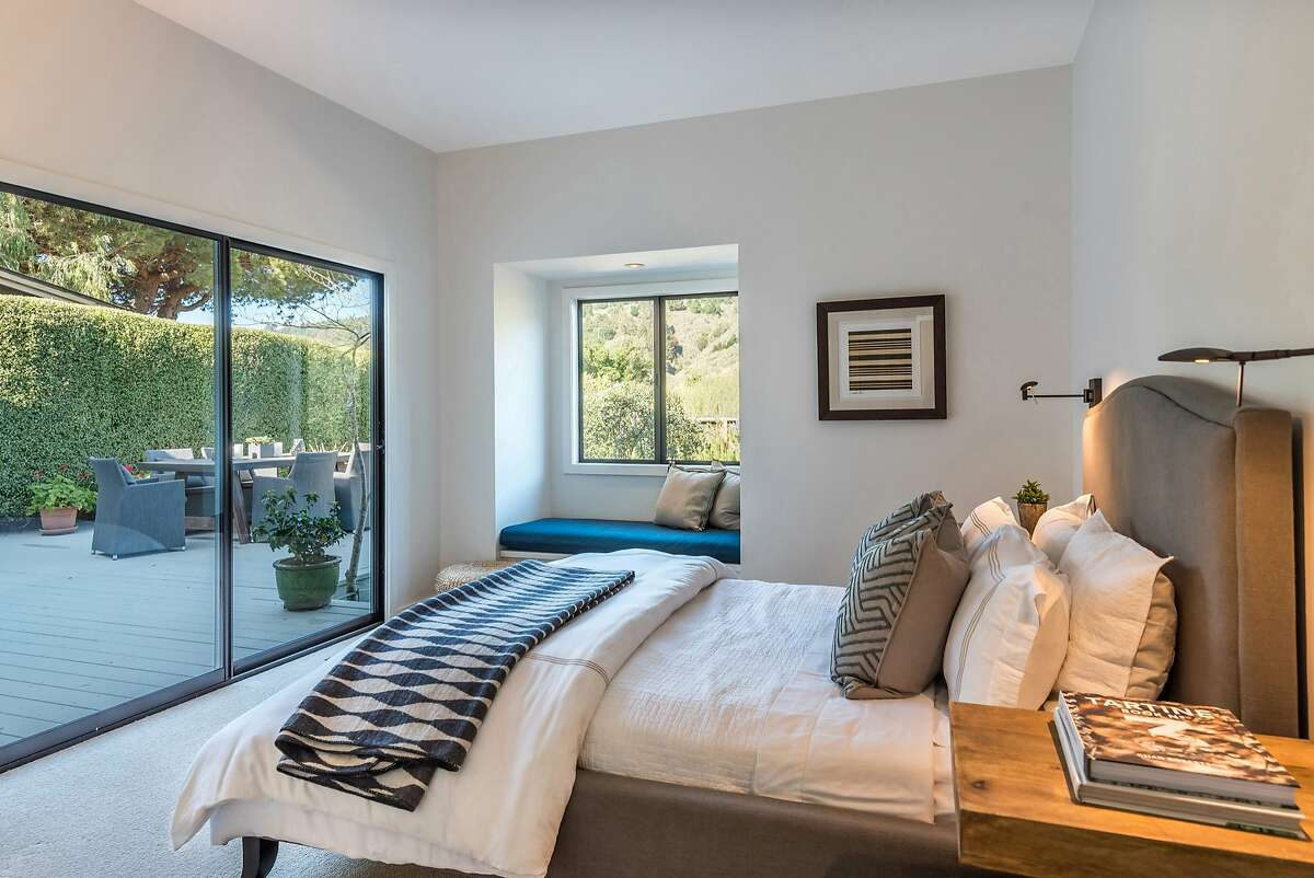 This bedroom includes a sitting window and deck access beyond a sliding glass door.