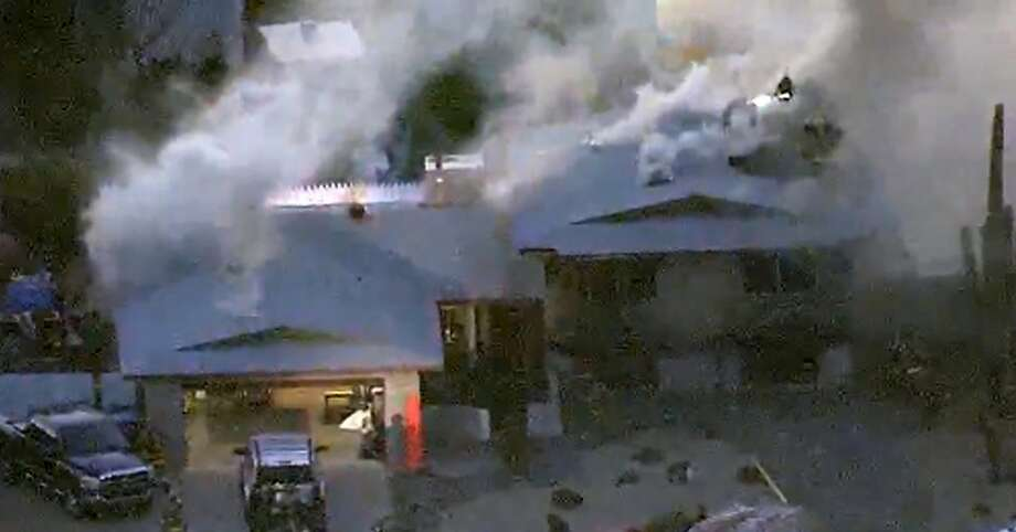 This image made from video provided by KNXV ABC-15 Arizona shows firefighters atop a house engulfed in flames in Phoenix on Tuesday, Feb. 23, 2016. Police and firefighters braved bullets and flames as they responded to the fatal shooting and house fire. (KNXV ABC-15.com via AP) TV OUT Photo: Associated Press